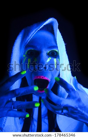 A woman is screaming in the black light with her mouth open.