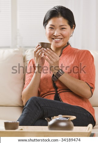 A woman is seated on her sofa, and drinking tea out of a tea cup.  She is smiling at the camera.  Vertically framed shot. - stock photo