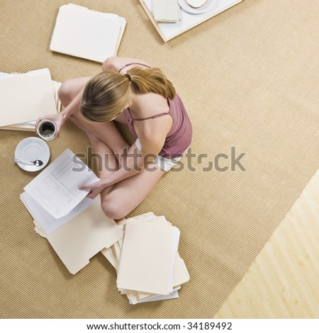 A woman is seated on the floor, looking through files, and drinking coffee.  Square framed shot. - stock photo