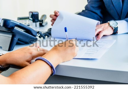 A woman is signing a legal document - stock photo