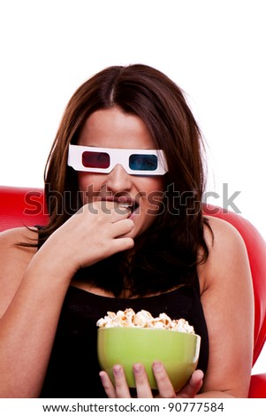 A woman is sitting on a red sofa watching a movie in 3D and eating popcorn. Woman watching 3D movie. - stock photo