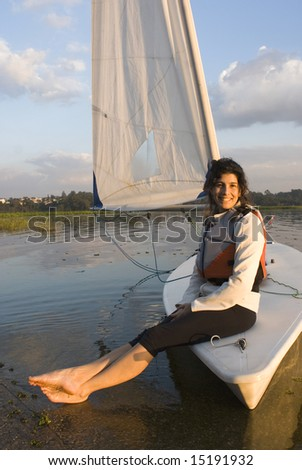 A woman is sitting on a sailboat.  She is smiling and looking at the camera.  Vertically framed shot. - stock photo