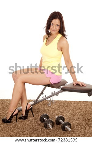 A woman is sitting on a workout bench wearing heels. - stock photo