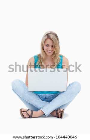 A woman is sitting on the ground looking at her laptop against a white background - stock photo
