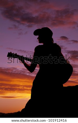 A woman is sitting with a guitar in the sunset. - stock photo