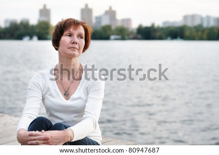 A woman is sittng on wood boards by the water - stock photo