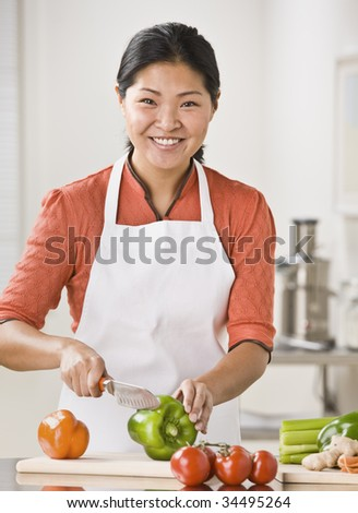 A woman is slicing produce in her kitchen.  She is smiling at the camera.  Vertically framed shot. - stock photo