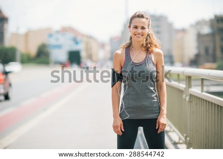 A woman is smiling happily as she takes a break on a bridge. She is relaxed, happy, and fit, and enjoying the workout in the sunshine. - stock photo