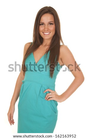 A woman is smiling while posing in a teal dress. - stock photo