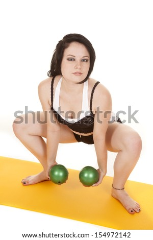 A woman is squatting and holding two green balls. - stock photo