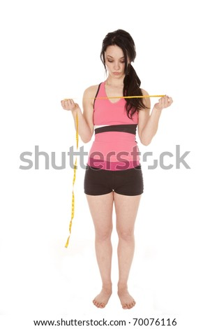 A woman is standing and holding a measuring tape dressed in shorts and a tank top.