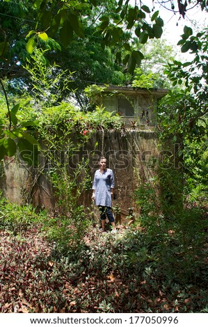 A woman is standing in front of an old abandoned building overgrown with vegetation, she is looking at viewer. - stock photo