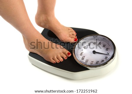 A woman is standing on a weight scale - stock photo