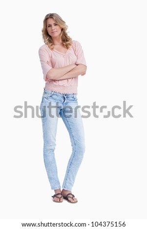 A woman is standing with her arms folded against a white background - stock photo