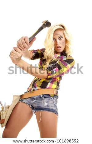 A woman is swinging a hammer.  She is in shorts and a plaid shirt. - stock photo