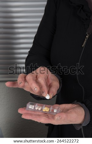 A woman is taking her tablets - stock photo