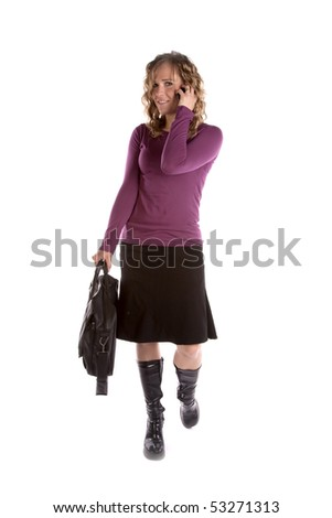 A woman is talking on her cell phone and walking with a smile on her face. - stock photo