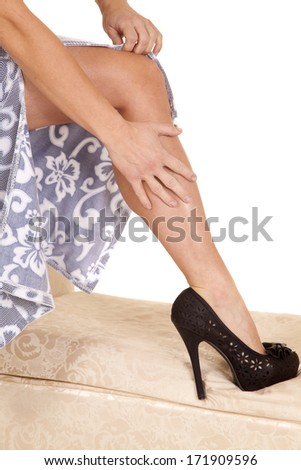 A woman is touching her leg wearing heels. - stock photo