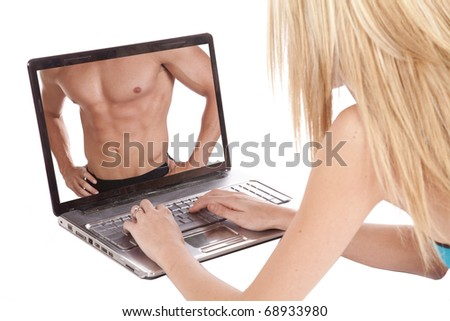 A woman is using her laptop and looking at the chest of a man.