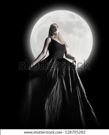 A woman is wearing a long black dress moving in the dark night against a full moon for a fashion or mystery concept. - stock photo