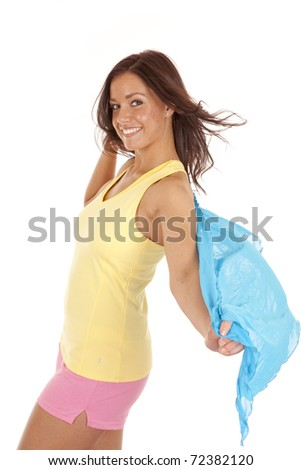 A woman is wearing a yellow tank top, pink shorts, and has a blue sarong. - stock photo