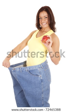 A woman is wearing very large pants and holding an apple. - stock photo
