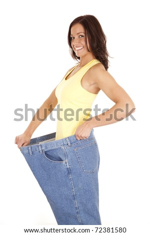A woman is wearing very large pants and showing off her weight loss. - stock photo
