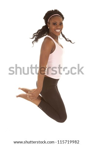 a woman jumping up in the air with a smile on her face.