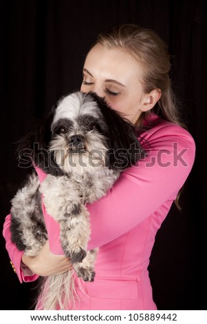 A woman kissing the top of her dogs head. - stock photo