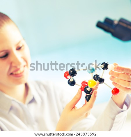 A woman laboratory assistant uses a computer for the simulation of organic molecules - stock photo