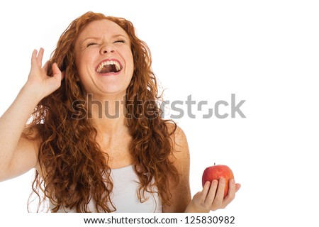 A woman laughing hysterically while holding a fresh apple