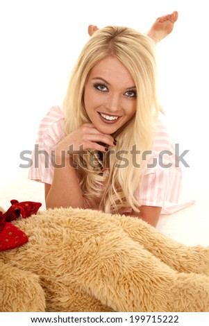 A woman laying down by her teddy bear with a smile.