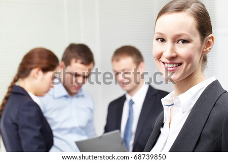 A woman leader standing against her colleagues - stock photo