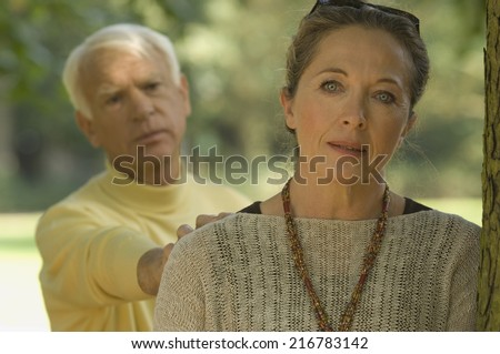 A woman leaning on a tree, man consoling her. - stock photo