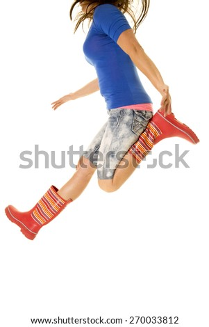 a woman leaping up in the air kicking her feet up. - stock photo
