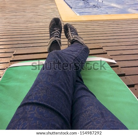 A woman legs in a summer chair resting in the outside of a spa in winter with the swimming pool at front of her. - stock photo