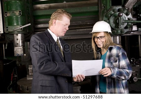 A woman listening to her boss while he shows her something on his blue print. - stock photo