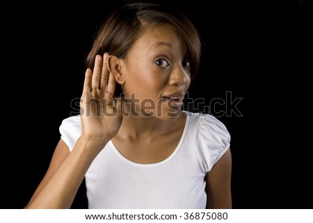 a woman listens intently with her hand to her ear - stock photo