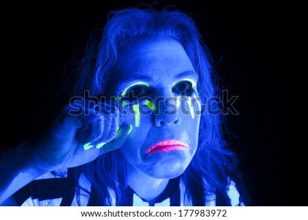A woman lit up by a black light is sad.