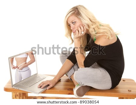 A woman looking at her laptop envy of the woman's body.