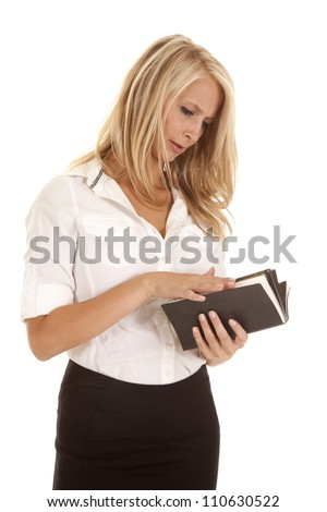 A woman looking down at a book reading with a concentrating expression on her face. - stock photo