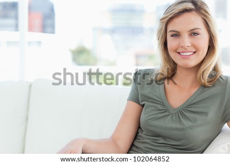 A woman looking in front of her while smiling as she sits on the couch.