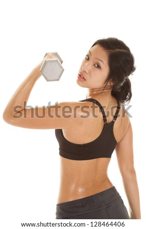 a woman looking over her shoulder doing an arm curl. - stock photo