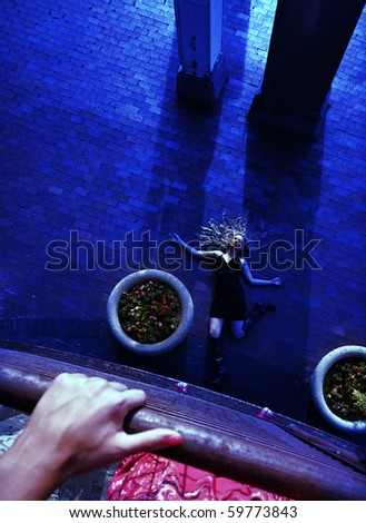a woman looks over a balcony at a woman on the ground - stock photo
