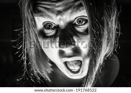 A woman looks scared to death as if she is screaming for help. - stock photo
