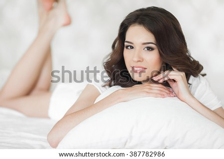 A woman lying at the end of the bed underneath the quilt and smiling, with her head resting upon her hand on pillow. young beautiful girl in a bed. Sensual woman lwith white pillow - stock photo
