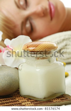 A woman lying behind a bottle with oil for spa treatment, focus on bottle - stock photo