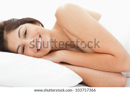 A woman lying on the bed, her head is on the pillow with her eyes open and smiling. Her hands are on the pillow while her arms are on the bed. - stock photo