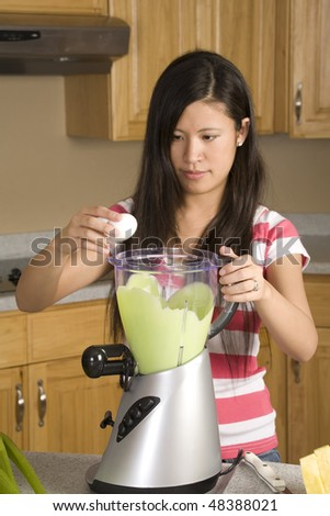 A woman making a great smoothie placing an egg in her drink to make it healthy. - stock photo