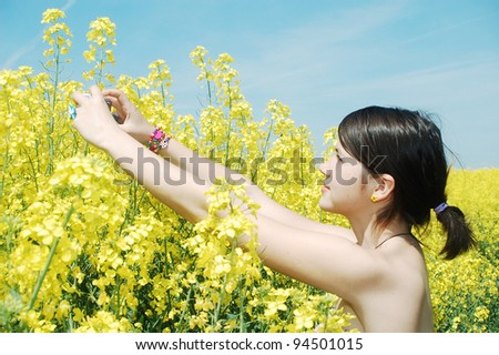 A woman making photos on a rapeseed field with her digital camera. - stock photo